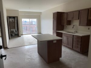 Continued installation of cabinets, solid surface countertops, LVT, carpeting and Magic-Pak HVAC in resident units.